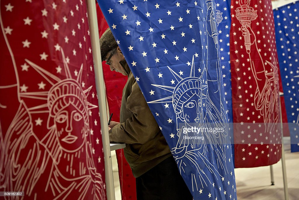 A man stands in a voting booth at a polling station in Manchester, New Hampshire, U.S., on Tuesday, Feb. 9, 2016. Voters in New Hampshire took to the polls today in the nations first primary in the U.S. presidential race. Photographer: Daniel Acker/Bloomberg via Getty Images