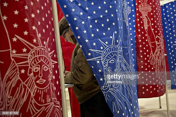 A man stands in a voting booth at a polling station in Manchester New Hampshire US on Tuesday Feb 9 2016 Voters in New Hampshire took to the polls...