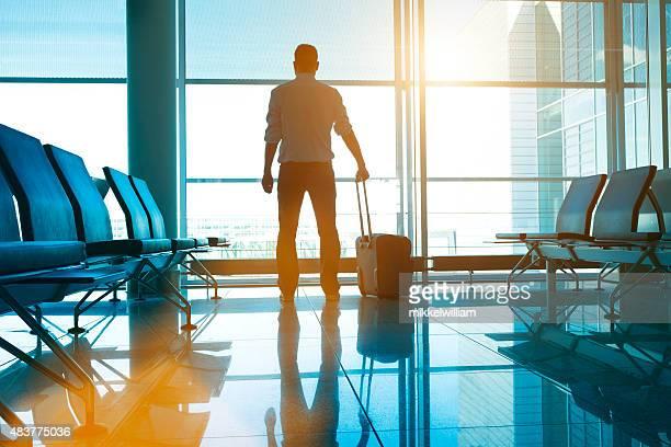 Mann steht im Flughafen mit Koffer wartet auf seinen Flug