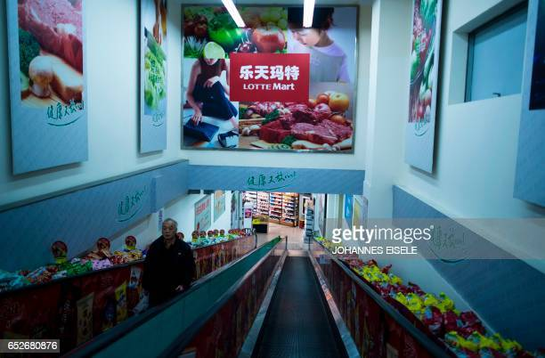 A man stands in an almost empty Lotte Mart in Shanghai on March 13 2017 The store remained open but dozens of other Lotte stores in China have been...