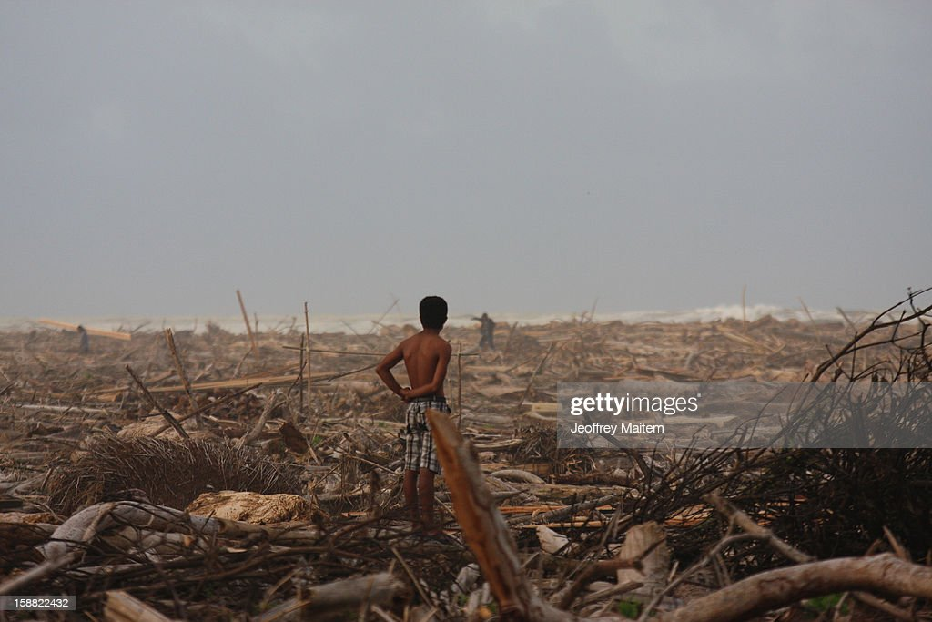 A man stands in coastal village devastated by super typhoon Bopha on December 29, 2012 in Cateel, Philippines. More than 1000 people have died and nearly a thousand remain missing after Typhoon Bopha, the strongest storm to hit the Philippines this year, pounded the region.