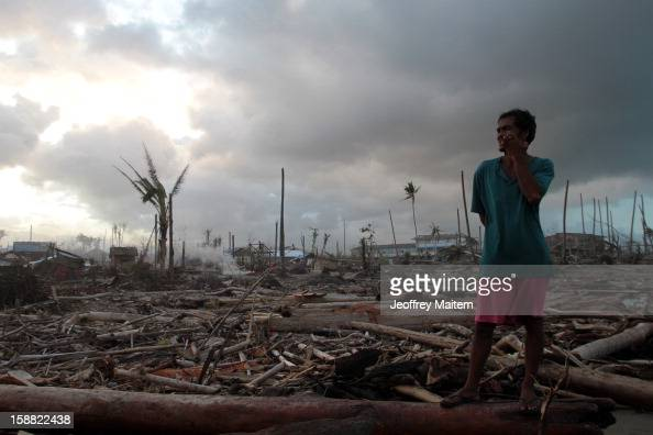 A man stands in coastal village devastated by super typhoon Bopha on December 29 2012 in Cateel Philippines More than 1000 people have died and...