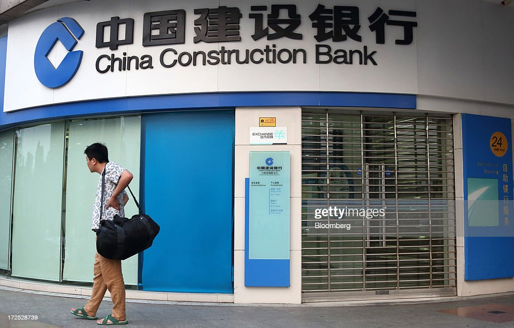 A man stands in front of a China Construction Bank Corp. branch in Shanghai, China, on Monday, July 1, 2013. Chinese banks' valuations are close to their lowest on record as the nation's interbank funding crisis exacerbated investors' concern that earnings growth will stall and defaults may surge as the economy slows. Photographer: Tomohiro Ohsumi/Bloomberg via Getty Images