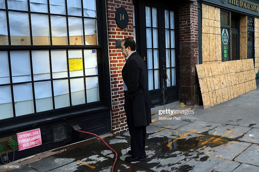 A man stands in front of a closed businesses affected by Superstorm Sandy in the heavily damaged South Street Seaport on December 3, 2012 in New York City. South street Seaport, an area popular with tourists which was about to go through a major redevelopment, suffered severe damage from Hurricane Sandy. Most of the buildings and businesses, including the South Street Seaport Museum, suffered severe flooding and remained closed. According to a new Siena Research Institute poll, most New Yorkers overwhelmingly agree that climate change was behind Hurricane Sandy.