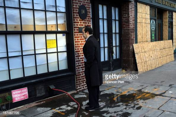A man stands in front of a closed businesses affected by Superstorm Sandy in the heavily damaged South Street Seaport on December 3 2012 in New York...