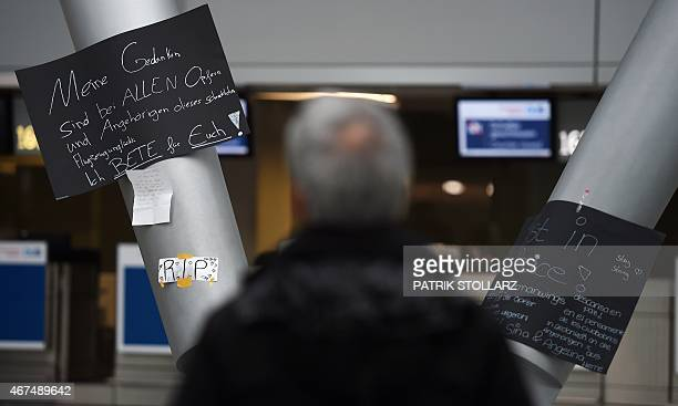 A man stands in front of a condolence message that reads 'My thoughts are at all victims and relatives of this horrible aviation disaster I pray for...