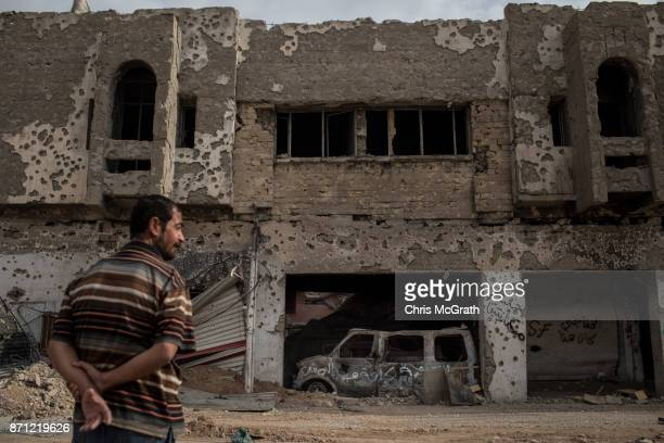 A man stands in front of a destroyed building in an outer neighborhood of the Old City in West Mosul on November 6 2017 in Mosul Iraq Five months...