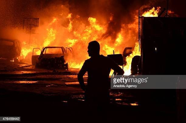 A man stands in front of a fire following a car bomb blast in Baghdad Iraq on June 9 2015 A Car bomb went off near restaurants and shop in Palestine...