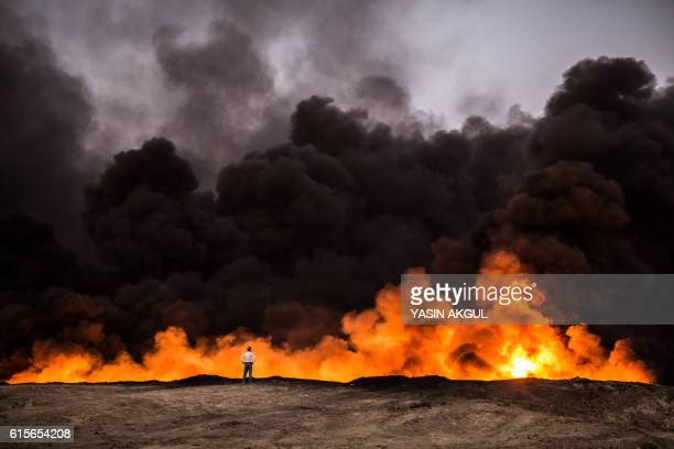 TOPSHOT A man stands in front of a fire from oil that has been set ablaze in the Qayyarah area some 60 kilometres south of Mosul on October 19 during...