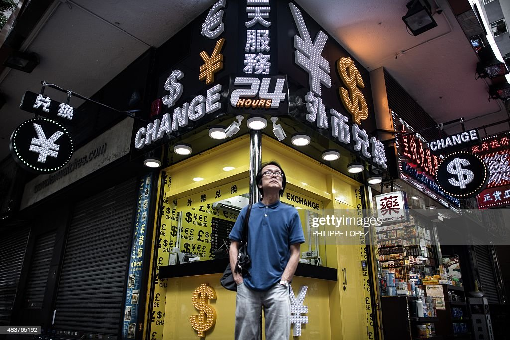 A man stands in front of a foreign currency exchange booth in Hong Kong on August 13 2015 China cut the reference rate for its currency for the third...