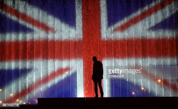 TOPSHOT A man stands in front of a fountain illuminated with the colours of the United Kingdom flag on May 23 in Zagreb during a tribute to victims...