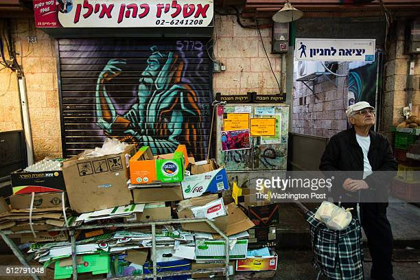 A man stands in front of a graffiti depicting a Jewish man praying which was painted over a closed shutter at the Mahane Yehuda Market often called...