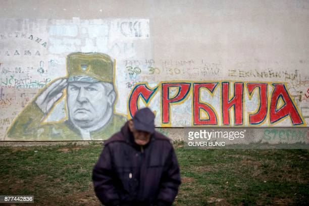 TOPSHOT A man stands in front of a graffiti depicting former Bosnian Serb commander Ratko Mladic and reading 'Serbia' written in Cyrillic painted on...