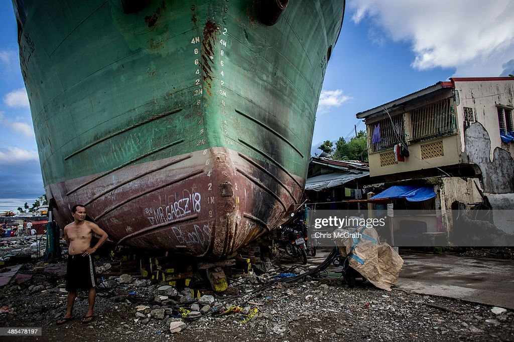 A man stands in front of a large ship grounded by Typhoon Haiyan on April 18, 2014 in Tacloban, Leyte, Philippines. People continue to rebuild their lives five months after Typhoon Haiyan struck the coast on November 8, 2013, leaving more than 6000 dead and many more homeless. Although many businesses and services are functioning, electricity and housing continue to be the main issues, with many residents still living in temporary housing conditions due to 'No Build' areas preventing them from rebuilding their homes. This week marks Holy Week across the Philippines and will see many people attending religious activities.