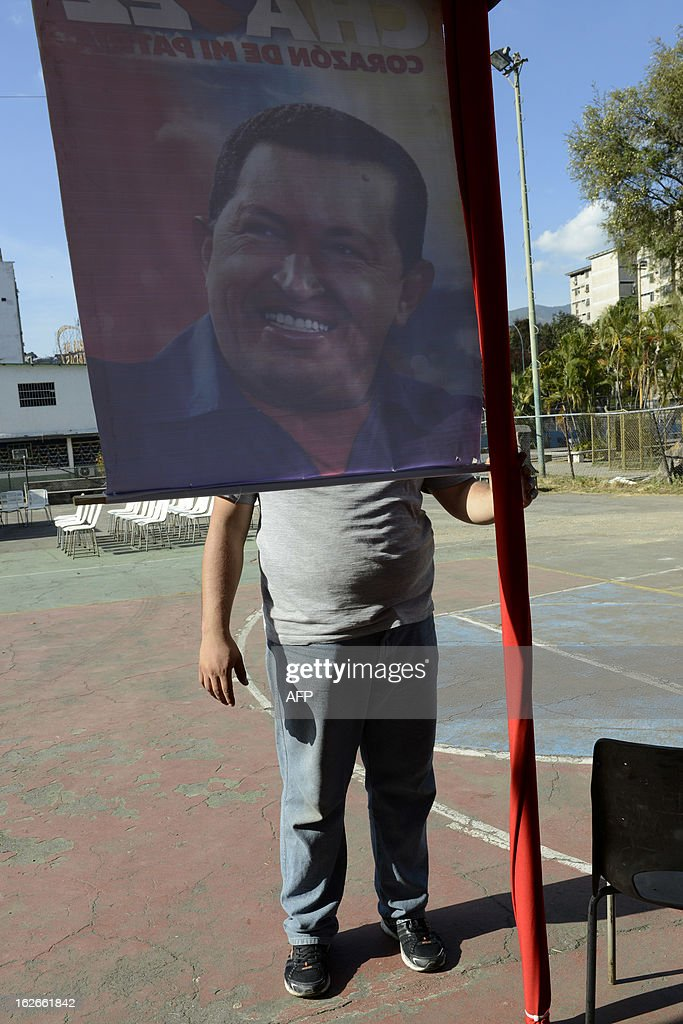 A man stands in front of a poster of Venezuelan President Hugo Chavez on February 25, 2013 in Caracas. Chavez has been hospitalized following his return from Cuba. The mystery surrounding the president's health has cast doubt over the political future of a nation sitting on top of the world's biggest oil reserve. AFP PHOTO/Leo RAMIREZ