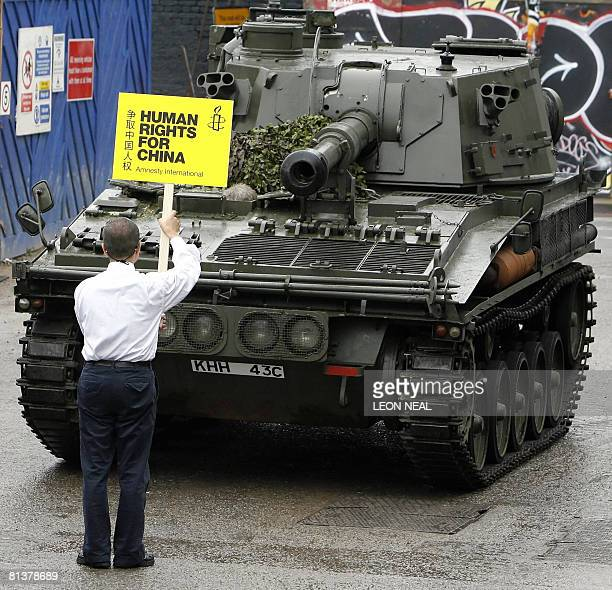 A man stands in front of a tank outside Amnesty International's headquarters in London on June 3 2008 to recreate the 'tank man' image of a lone...