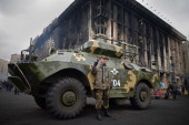 A man stands in front of an armored vehicle to have his picture take in Independence Square where dozens of protestors were killed in clashes with...