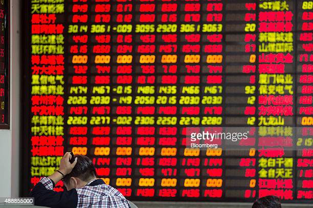 A man stands in front of an electronic board displaying share prices at a securities exchange house in Shanghai China on Friday Sept 18 2015 China's...