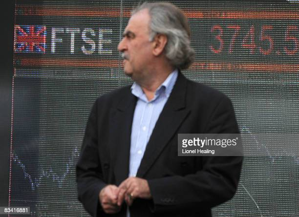 A man stands in front of an electronic sign showing the FTSE 100 share index on October 24 2008 on London England The FTSE fell by more than 300...