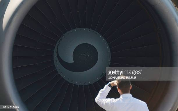 A man stands in front of an turbine of an airplane at the International Air Show ILA in Schoenefeld near Berlin on September 11 2012The 2012...