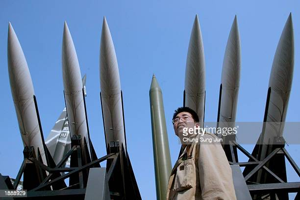 A man stands in front of at North Korean and South Korean missiles at the Korea War Memorial Museum April 1 2003 in Seoul South Korea According to...