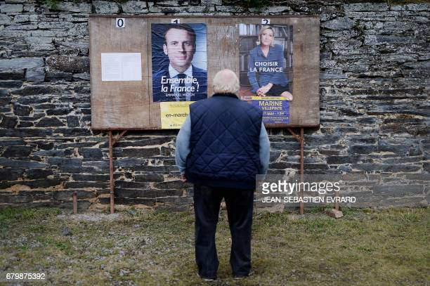 TOPSHOT A man stands in front of election posters near a polling station during the second round of the French presidential elections on May 7 2017...