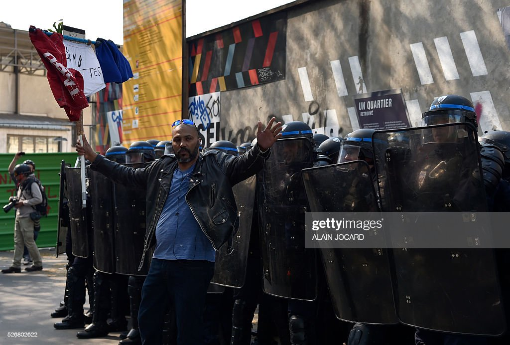 A man stands in front of French anti riot police during a clash with protesters during the traditional May Day demonstration in Paris on May 1, 2016.