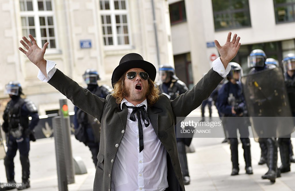 A man stands in front of French riot police during a protest against controversial labour reforms, on June 28, 2016 in Nantes, western France. People took to the streets in France on June 28 in the latest protest march in a marathon campaign against the French Socialist government's job market reforms. Last month the government used a constitutional manoeuvre to push the bill through the lower house without a vote in the face of opposition from Socialist backbenchers. / AFP / LOIC