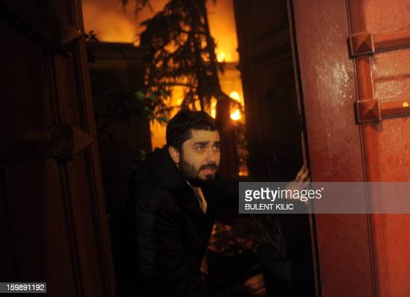 A man stands in front of Galatasaray University gate as Istanbul fireteams try to control flames during a fire at the University on January 22 in...