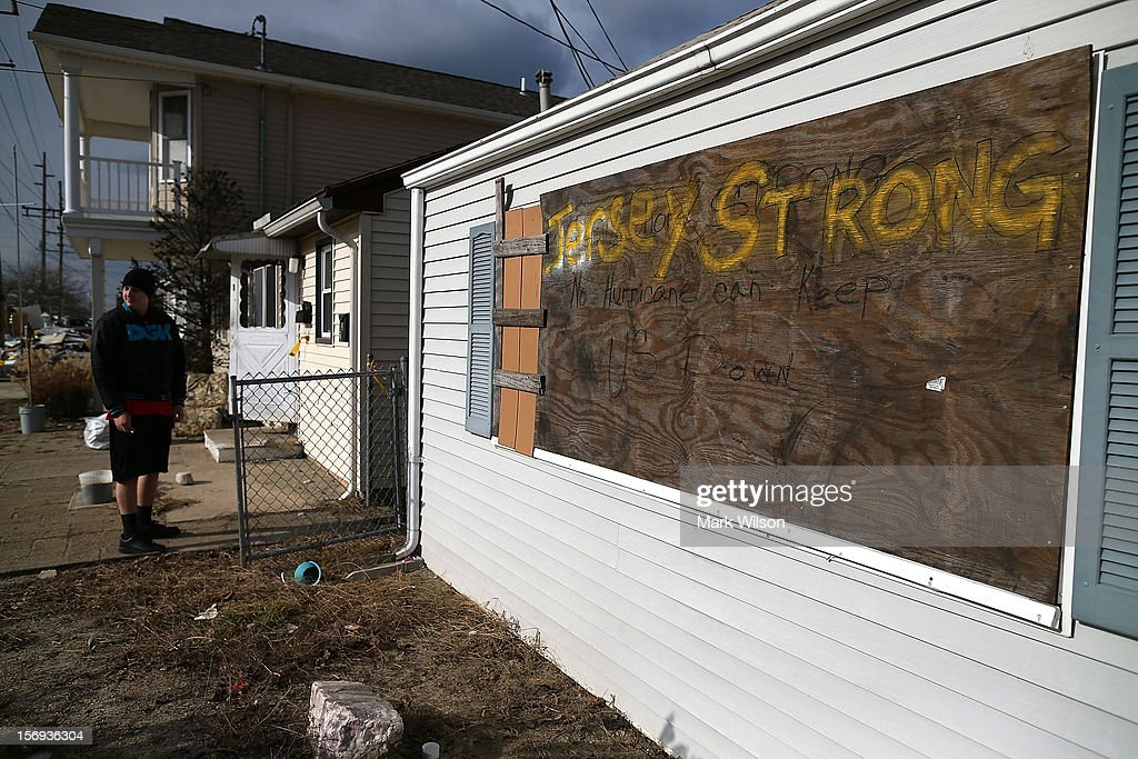 A man stands in front of his home that was flooded by Superstorm Sandy on November 25, 2012 in Seaside Heights, New Jersey. New Jersey Gov. Christie estimated that Superstorm Sandy cost New Jersey $29.4 billion in damage and economic losses.