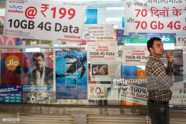 A man stands in front of posters and banners advertising the services of various mobile networks displayed in the window of a store at the Nehru...