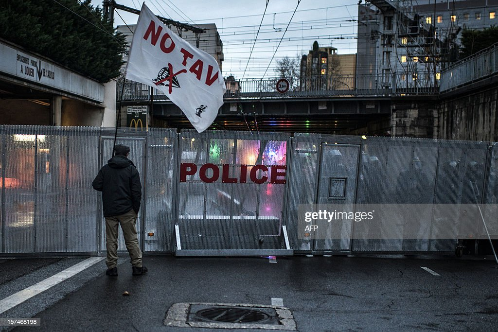 A man stands in front of riot police during a demonstration against the new LGV Lyon-Turin project, on December 3, 2012 in Lyon, on the sideline of the 30th France-Italy annual summit. AFP PHOTO / JEFF PACHOUD