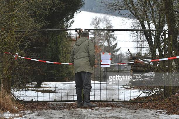 A man stands in front of the fence blocking the access to the private property where six teenagers were found dead in Arnstein central Germany on...