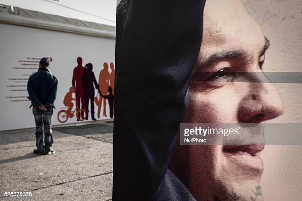 A man stands in front of the preelection campaign kiosk of SYRIZA and a poster showing the portrait of Alexis Tsipras leader of the party in Athens...