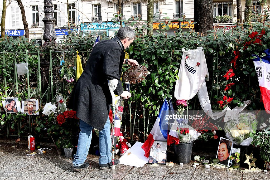 A man stands in front of the tributes to the victims of the Paris Attacks across the road from of 'Bataclan Cafe'on February 13, 2016 in Paris, France. People continue to leave tributes to victims three months after the Paris terrorist attacks.