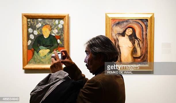 A man stands in front of Vincent van Gogh's 'Woman Rocking a Cradle' and Edvard Munch's 'Madonna' as he takes a picture during a press preview of the...