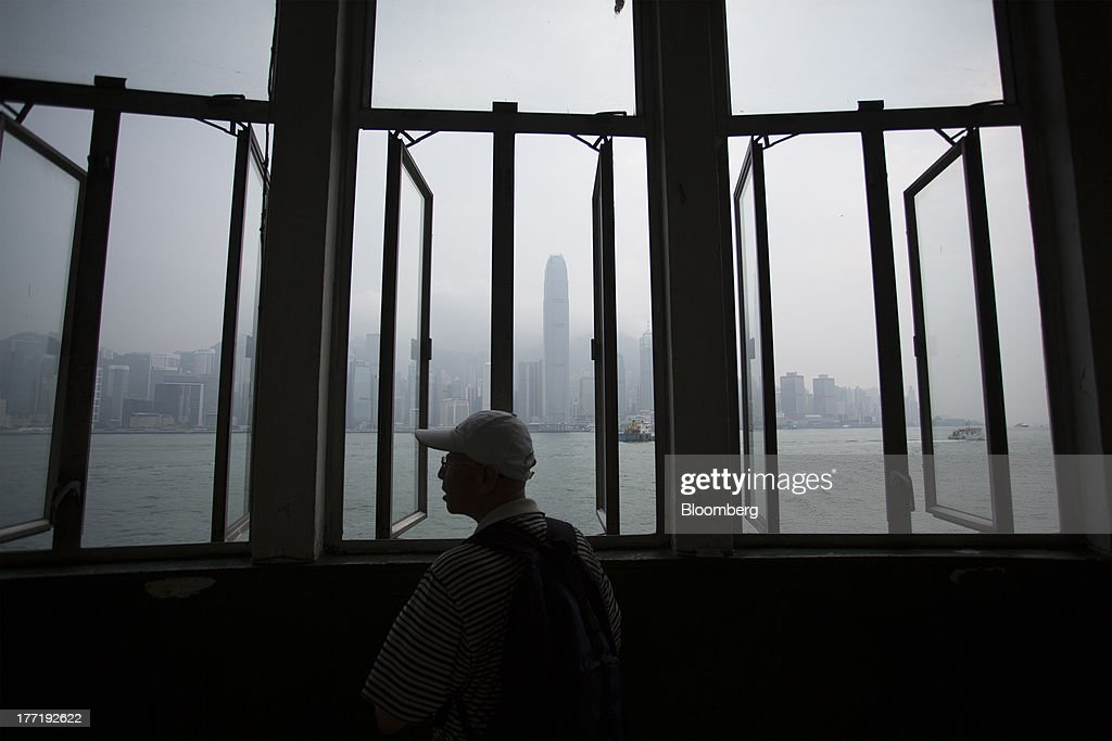A man stands in front of windows facing the Hong Kong island skyline in the Tsim Sha Tsui area of Hong Kong, China, on Thursday, Aug. 22, 2013. Hong Kongs air pollution index reached very high level today as a tropical storm that passed through Taiwan trapped pollutants and blanketed the city in haze, triggering a government health warning. Photographer: Jerome Favre/Bloomberg via Getty Images