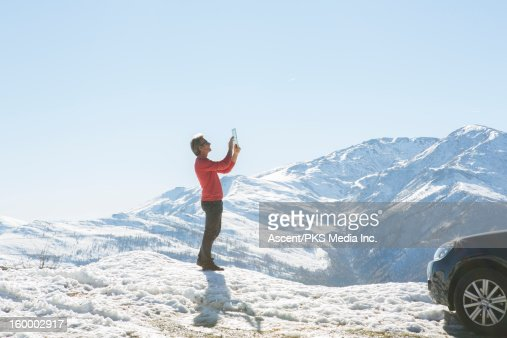 Man stands in snow, takes pic with digital tablet : Stock Photo