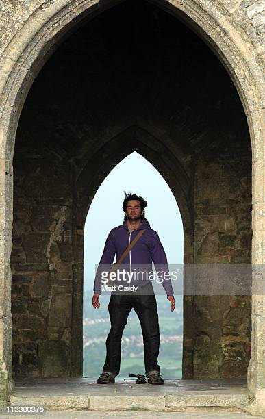 A man stands in the doorway as druids and pagans conduct a May Day dawn celebration service in front of St Michael's Tower on Glastonbury Tor on May...