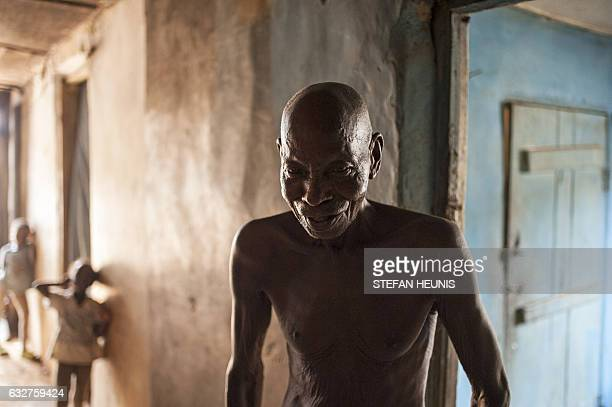 A man stands in the hallway of a shared accommodation house where families rent rooms on January 6 2017 in Lagos Nearly two years after taking office...