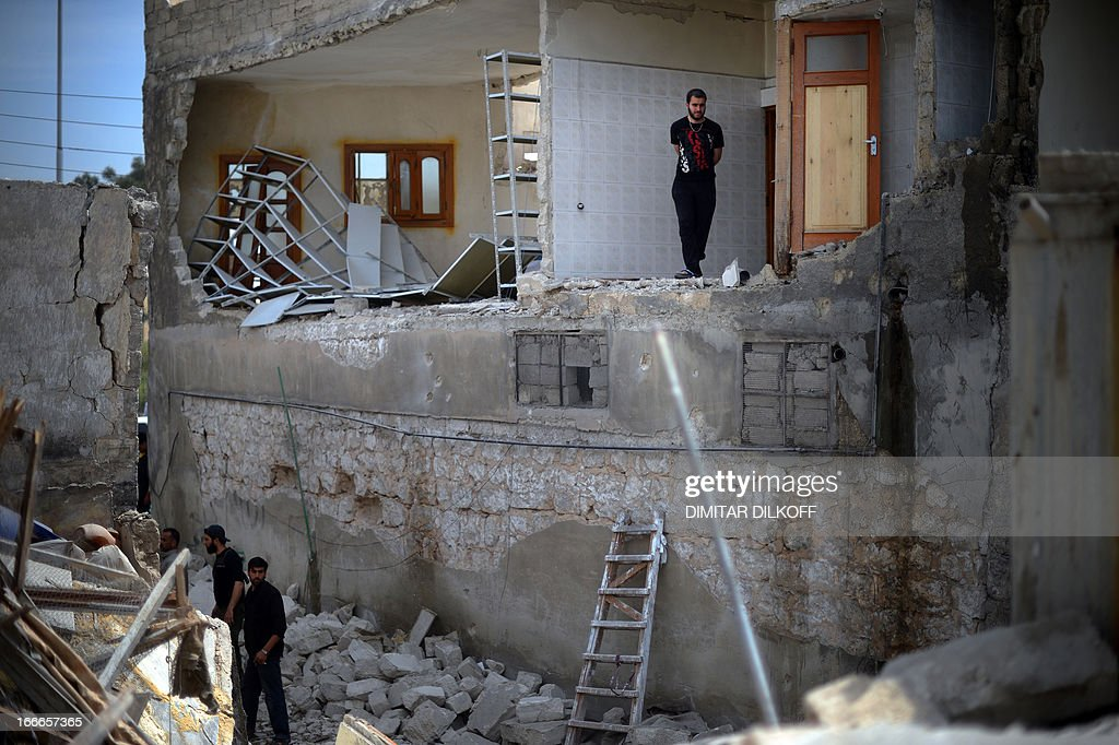 A man stands in the remains of a destroyed house following an airstrike by the Syrian airforce in the northern Syrian city of Aleppo on April 15, 2013. The conflict in Syria, which is now in its third year, has cost 70,000 lives, according to the United Nations.