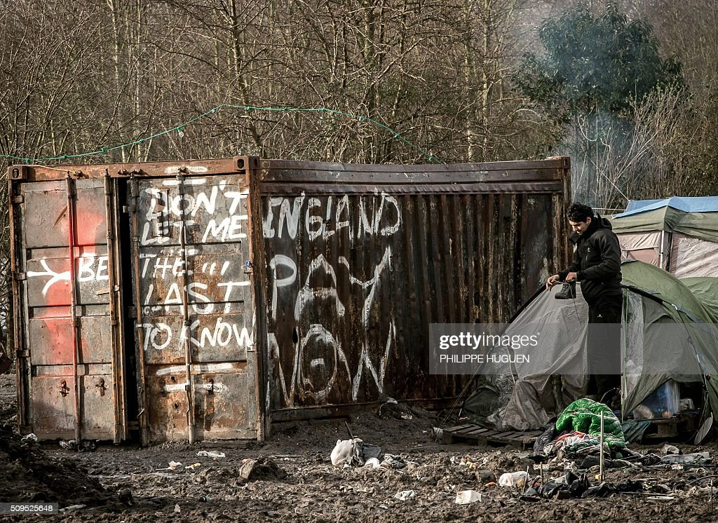 A man stands in the so-called 'Jungle' migrant camp in Gande-Synthe where 2,500 refugees from Kurdistan, Iraq and Syria live on February 11, 2016 in Grande-Synthe near the city of Dunkirk, northern France. / AFP / PHILIPPE HUGUEN