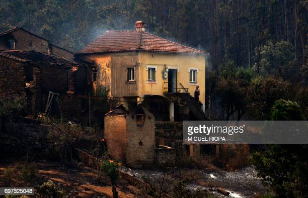 A man stands in the stairway of a house with smoke billowing from the roof in an area devastated by a wildfire in Canical near Alvares on May 18 2017...