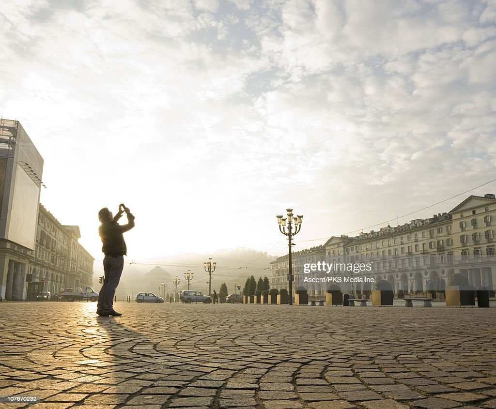 Man stands in urban piazza, takes pic with cell