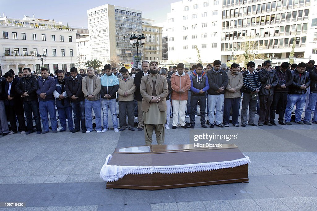 A man stands near a coffin as members of an Athen's Pakistani community gather near the body of a 27-year-old Pakistani migrant who was a victim of an alleged racism-fuelled crime on January 19, 2013 in Athens, Greece. Hundreds of Greeks and other nationals marched peacefully against racism on January 19. Long standing as a hub for immigration from the Middle East, Africa and Asia, Greece is under pressure with racial issues as the economic crisis warps the burdens of blame in struggling communities.
