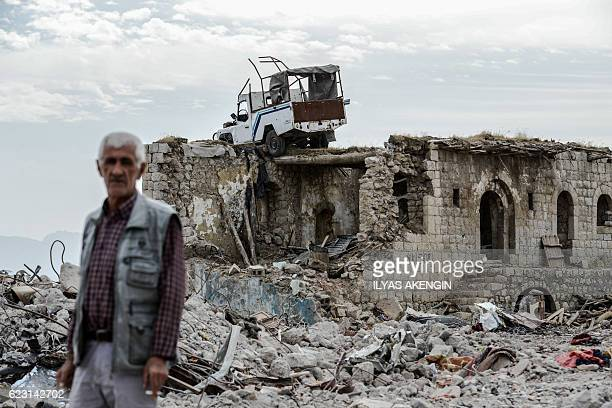 TOPSHOT A man stands near a damaged building upon his arrival in Sirnak city on November 14 2016 after a 246day curfew was partially lifted The...