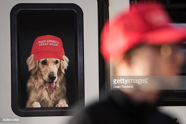 A man stands near a Donald Trump campaign vehicle with an image of a dog in a window before a campaign rally February 5 2016 in Florence South...