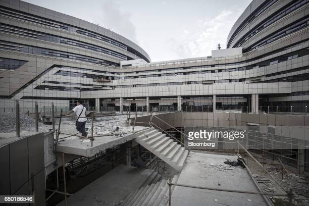 A man stands near a flight of stairs at the construction site of the Evergrande International Hospital inside the Hainan Boao Lecheng...