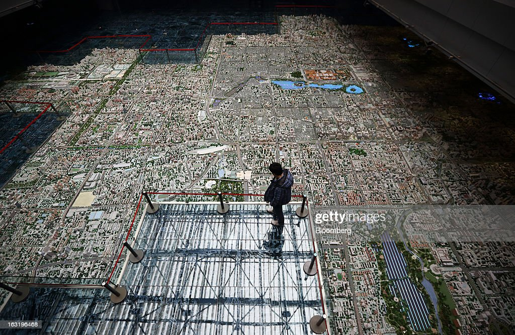 A man stands near a model of the city of Beijing at the Beijing Planning Exhibition Hall in Beijing, China, on Wednesday, March 6, 2013. China maintained its economic-growth target at 7.5 percent for 2013 while setting a lower inflation goal of 3.5 percent, setting up a challenge for new leaders to keep prices in check without harming expansion. Photographer: Tomohiro Ohsumi/Bloomberg via Getty Images