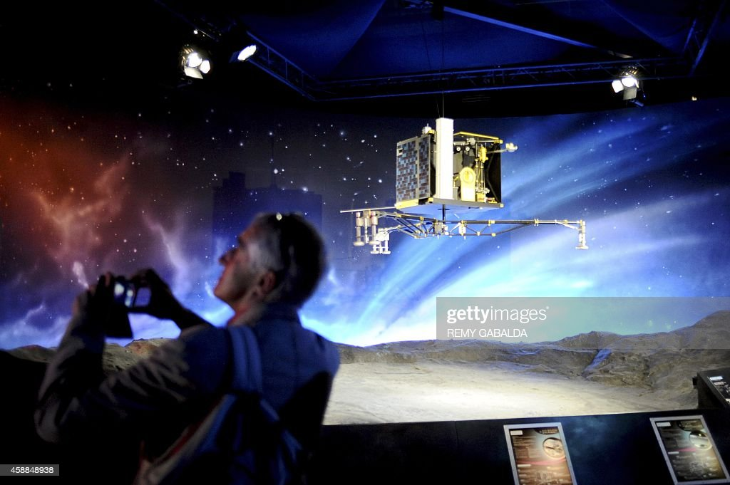 A man stands near a model of the European Space Agency's robot craft Philae as he visits the Cite de l'espace in Toulouse southern France on November...